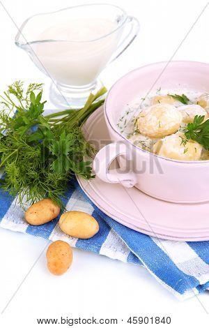 Concursos jovens batatas com creme de leite e ervas na panela isolado no branco