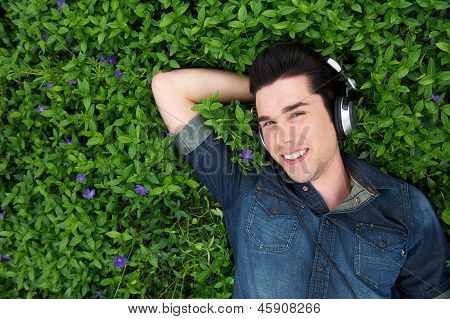 Attractive Young Man Lying On Grass Listening To Music On Headphones