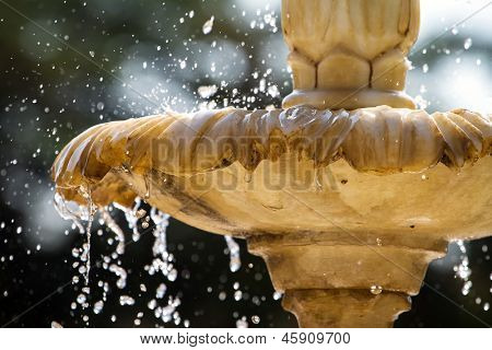 Close-up of an old stone fountain with dripping water and blurred background