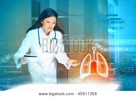 Image of pretty woman therapist examining virtual image of lungs