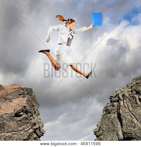 Image of young businesswoman jumping over gap