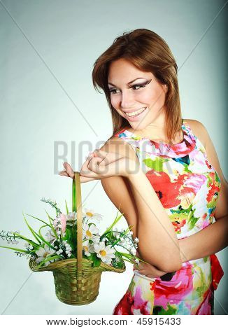 Attractive Smiling Brunet Girl In Colorful Dress With Flowers Basket,studio Shot,gray Background