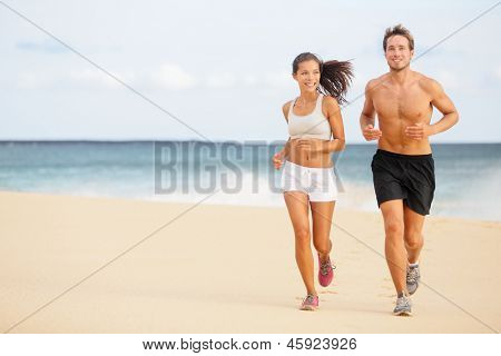 Runners. Young couple running on beach. Athletic attractive people jogging in summer sport shorts enjoying the sun exercising their healthy lifestyle. Multiethnic couple, Asian woman, Caucasian man.