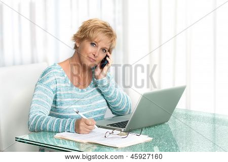Middle aged woman talking on phone and working on a laptop from home.