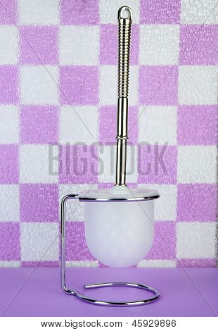 Toilet brush on tile wall background