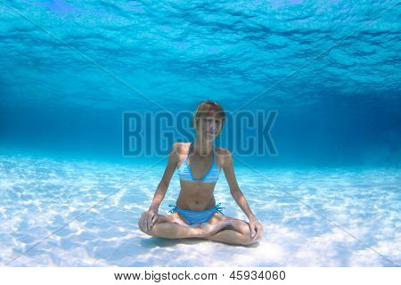 Young woman holding a breath and relaxing on a sandy bottom in a yogic lotus position