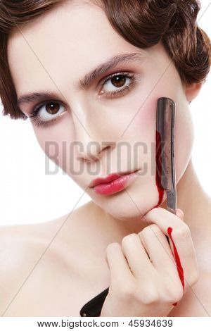 Close-up portrait of beautiful woman with bloody vintage razor in her hand, over white background