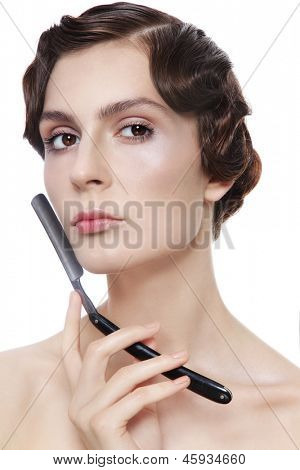 Beautiful woman with vintage razor in her hand, over white background