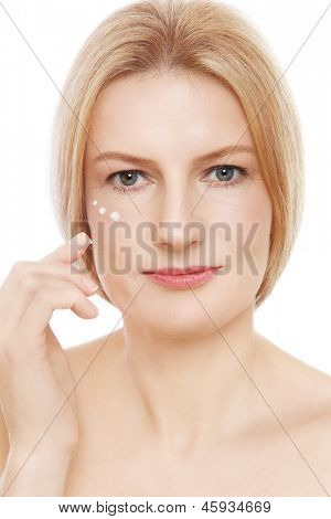 Portrait of mature beautiful healthy woman applying cream on her face, over white background