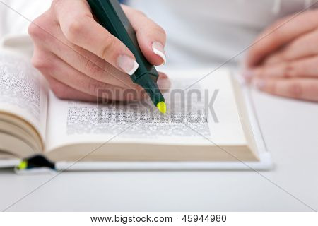 Highlighter  in female hand  marked text in book, education concept
