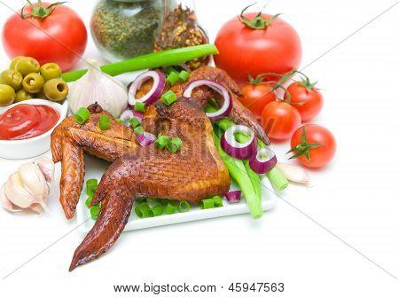 Geräucherter Hähnchenflügel mit Gemüse, Oliven und Ketchup auf einem weißen Hintergrund