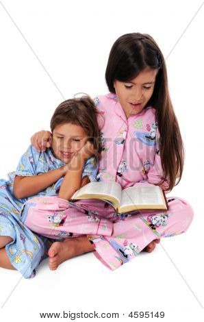 Girl Reading Bedtime Story To Sister