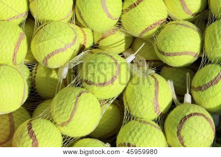 Clear netting bags filled with bright tennis balls