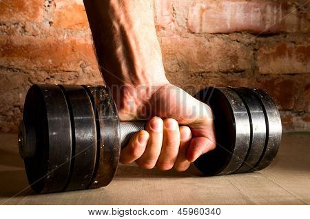 male hand is holding metal barbell against brick wall