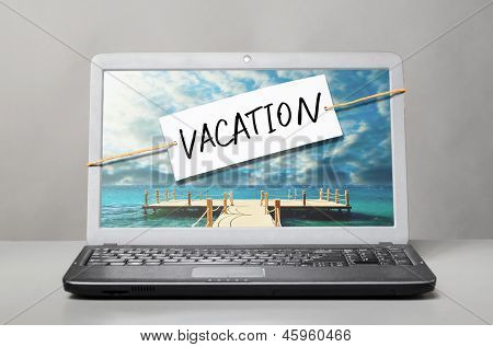 laptop with note about vacation