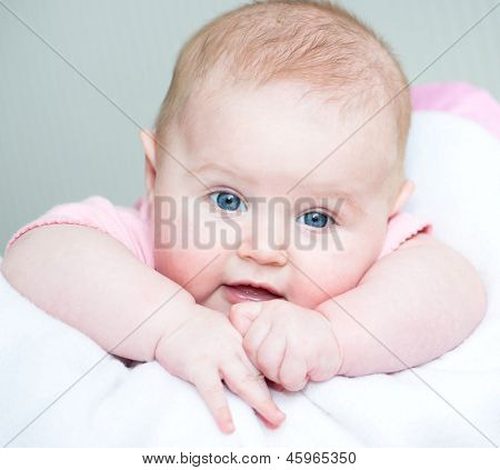 three month old baby  lye on a bed