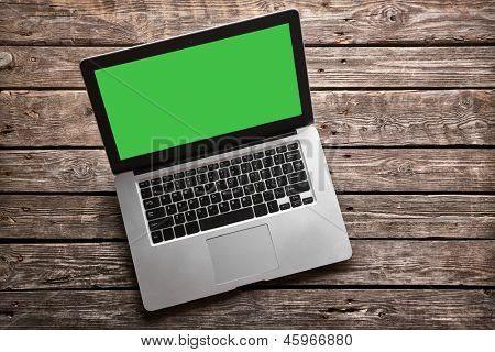 Open laptop with isolated green screen on old wooden desk.
