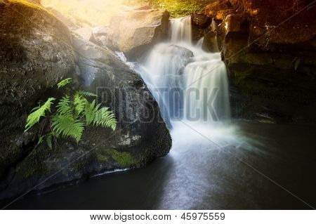 Beautiful waterfall on a mountain river with light coming from top