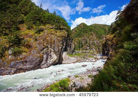 Dudh Kosi River In Khumbu Walley In Nepal And Foot Suspension Bridge Over It