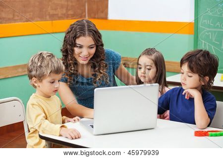 Beautiful teacher and students using laptop in class