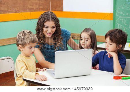 Linda professora e alunos usando o laptop na classe