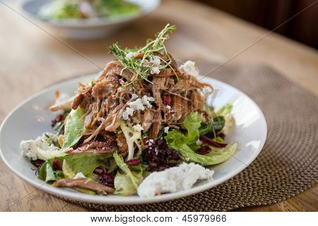 Closeup of garnished chicken salad at table in restaurant