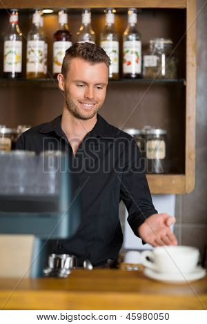 Handsome young barista gesturing at counter in coffeeshop
