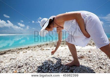 Caucasian Woman Collecting Seashells At The Beach