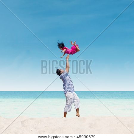 Dad Throwing Daughter In Air At Beach
