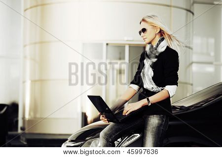 Business woman with laptop sitting on the car