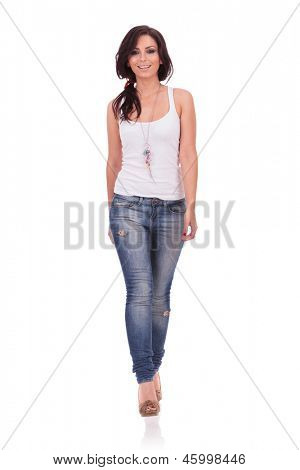 full length picture of a casual young woman walking straight toward the camera with a smile on her face. on white background