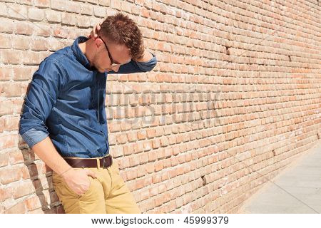 casual young man standing with a hand in his pocket and the other at the back of his head while looking down with melancholy, next to a brick wall