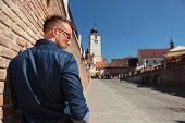 stock photo of sibiu  - back view of a casual young man standing next to a brick wall in Sibiu city - JPG