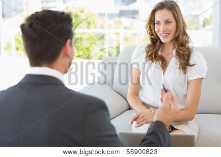 Smiling young woman in meeting with a financial adviser at home