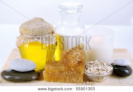 Honey and milk spa with oils and honey isolated on white