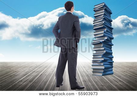 Businessman standing with hands on hips against stack of books against sky