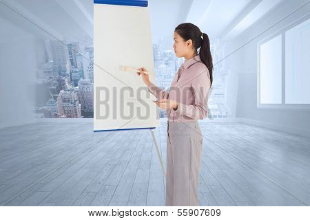 Businesswoman painting on an easel against city scene in a room