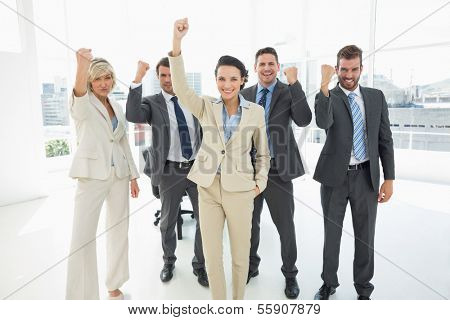 Portrait of a successful business team clenching fists in a bright office