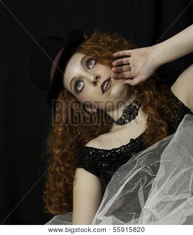 Young woman with long red hair wearing top hat