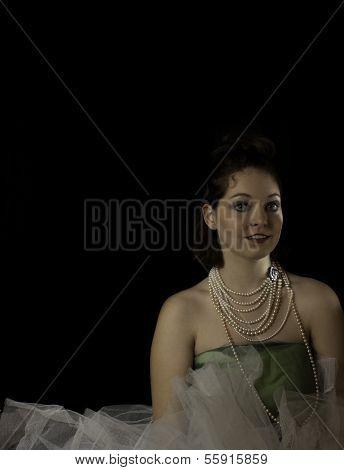 Beautiful woman wearing pearls, crinoline and green tulle