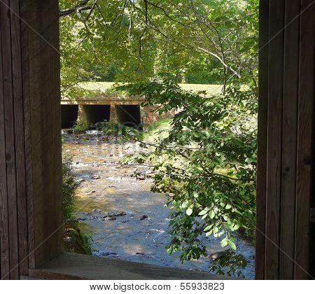 Creek Framed By Bridge Window