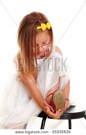 Cute Little Girl White Dress Putting On Her Shoe
