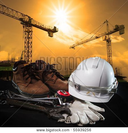 Helmet And Construction Equipment With Building And Crane Against Dusky Sky Use For Construction Bus