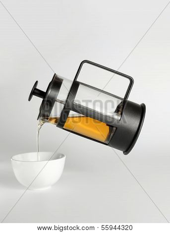 Tea Pouring From The French Press In A White Cup