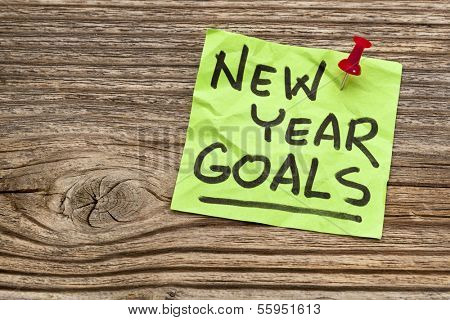 New Year goals - handwriting on a sticky note against grained wood