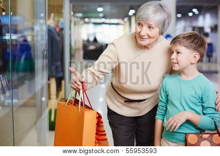 Portrait of cute child and his grandmother with paperbags looking at shop window