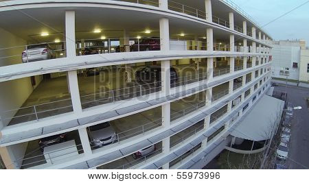 Cars parked in multistoried parking at evening. View from unmanned quadrocopter