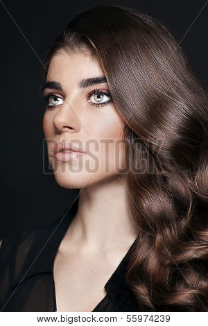 Portrait of young beautiful woman with curly brown hair