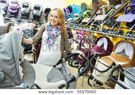 Young pregnant woman choosing baby carriage or pram buggy for newborn at shop store