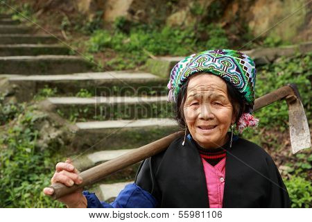 Asian Elderly Chinese Woman Farmer Peasant With Hoe On Shoulder.